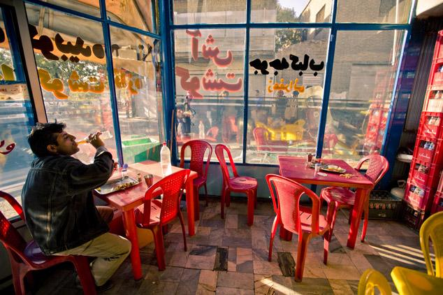 Cafe with red chairs, Tehran by James Longley