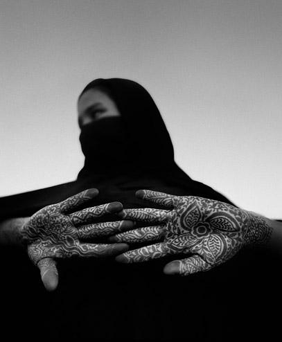 Young Moroccan woman with henna design on her hands by Chris Rainier
