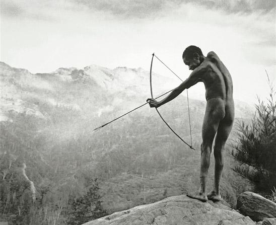 Young boy with arrow by Chris Rainier