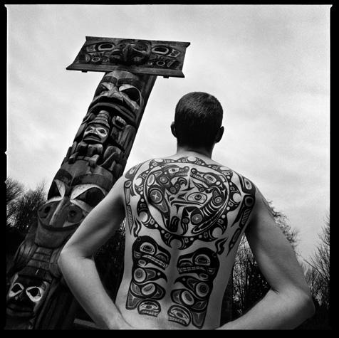 Man with Haida tattoos, totem poles by Chris Rainier