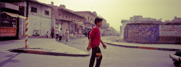 Boy walking, Baghdad by James Longley