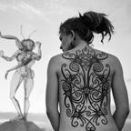 Sculpture and woman with back tattoos