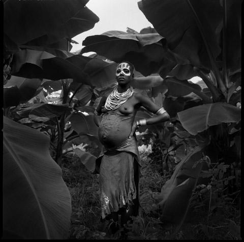 Pregnant Karo woman with scars, banana tree forest by Chris Rainier