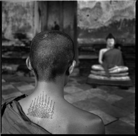 Young Thai Monk with Buddhist tattoos, meditating by Chris Rainier