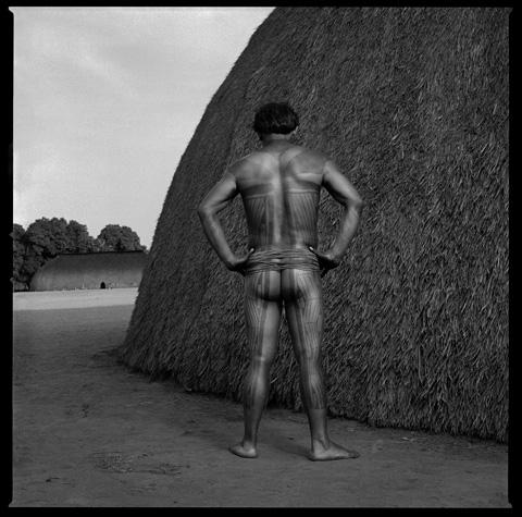 Tattooed Xingu man with traditional shobono house by Chris Rainier