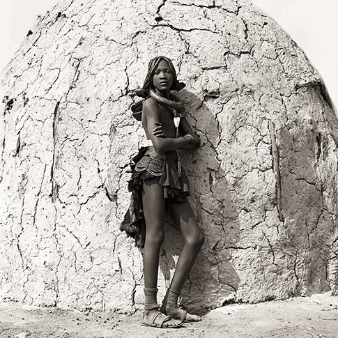 Himba Teen-age Girl and Traditional Hut, Kaokoland, Namibia, 2007 by Dana Gluckstein
