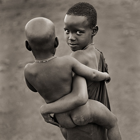 Njemp Sister Carrying Brother, Kenya, 1985 by Dana Gluckstein